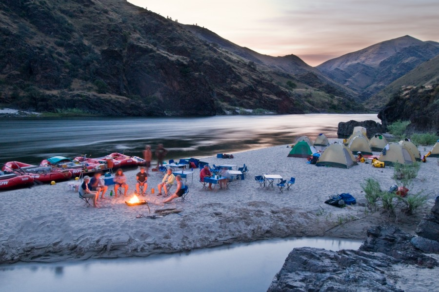 Idaho. Lower Salmon River. Camp on sandy beach with people around fire. MR